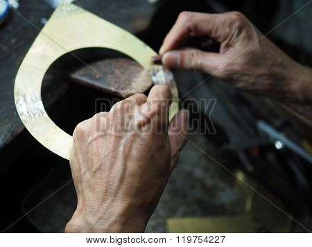 Goldsmith working on an unfinished  gold with his hard working hands