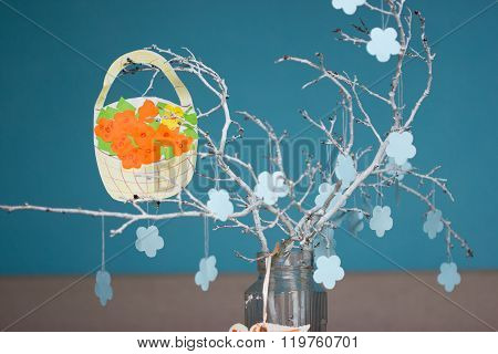White branch with papers flower and bucket on it. Blue background.