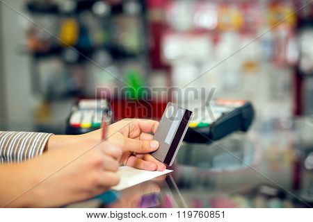 Woman holding credit card in hand, signing slip