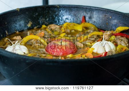 Meat With Potatoes, Apples And Garlic  In A Cauldron On Fire