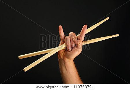 Man Hand With Crossed Drumsticks And Devil Horns Over Black