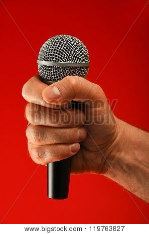 Man Hand With Microphone Over Red Background