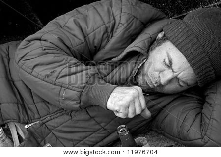 A homeless man sleeping on the streets and coughing. B & W and film grain effect added for drama.