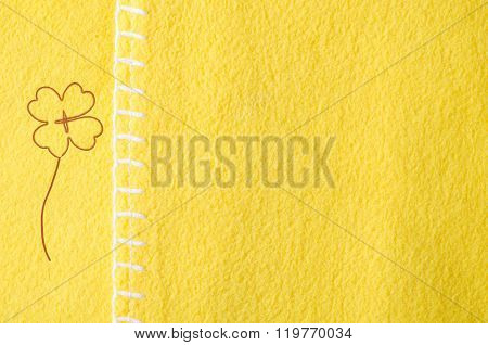 a background yellow fabric with seam and shamrock