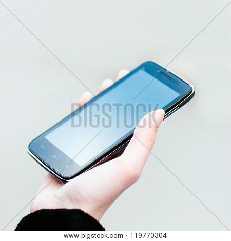 blank  widescreen smartphone in the woman's hand