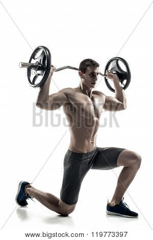 Mighty man standing on knee and holding barbell