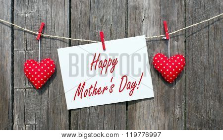 Happy Mother's Day sign or postcard and red hearts on wooden background