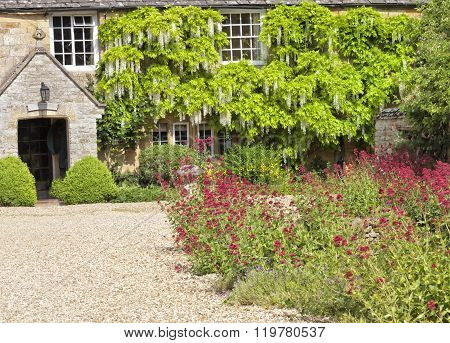 Cotswold stone manor house with cottage garden in front