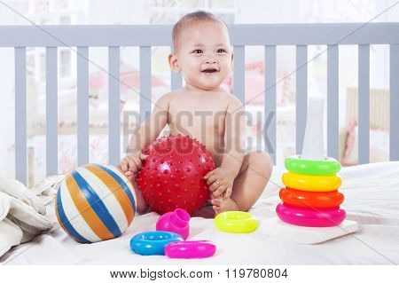Cheerful Baby Playing With Toys In Baby Crib