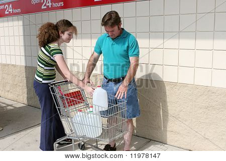 A father and daughter shopping for hurricane supplies.  Their cart is full of water jugs.  Image also appropriate for recycling.