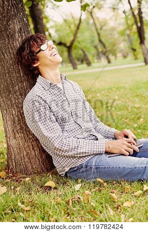 Young hispanic man wearing black glasses, checkered shirt and blue jeans sitting on grass under tree in autumn park, holding notebook and pen in his hands and laughing - laughter concept