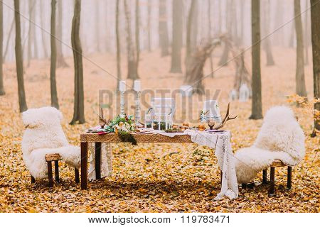 Dreamlike wedding table decorated in scandinavian style in the autumn forest