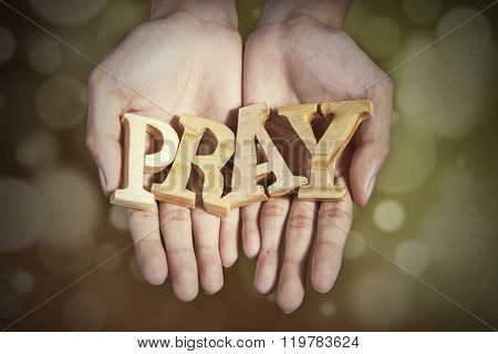 Hands With A Word Of Pray In Bokeh Background