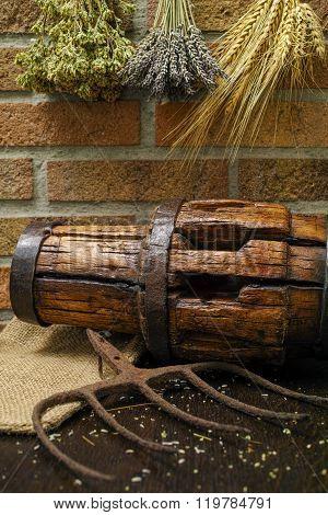 Antique Pitchfork And Wooden Wheel Hub On Burlap Sack