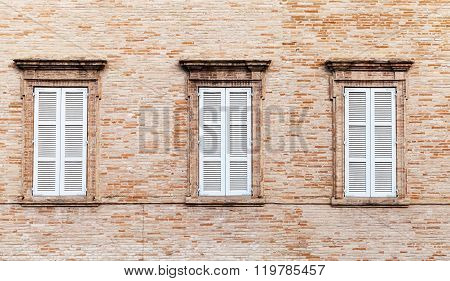 Three Windows With White Closed Wooden Shutters