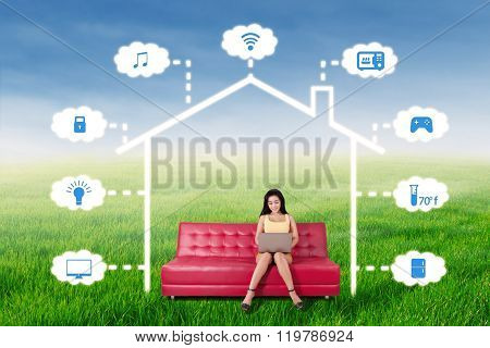 Woman Controlling A Smart House With Laptop