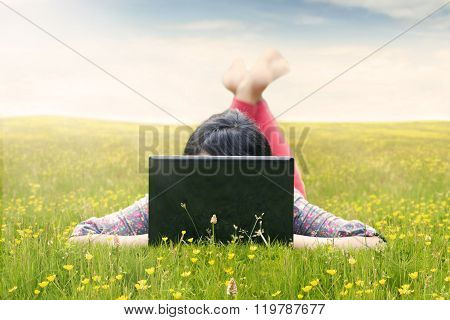 Woman Using Laptop In The Meadow