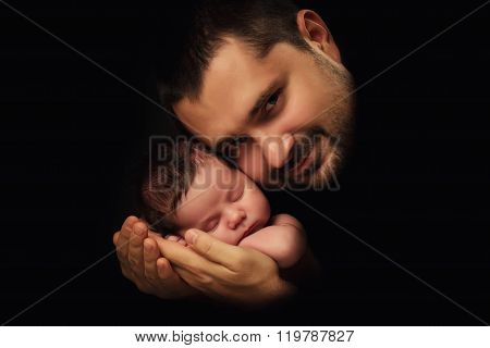 Daddy Hugs His Newborn Baby. Father 's Love.  Close-up Portrait On A Black Background