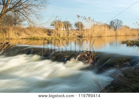 Flowing Water In The River, Coastal Vegetation Dispelled By Wind