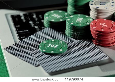 Casino chips and cards on laptop to play gambling online.