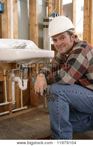 A friendly plumber installing bathroom fixtures on a construction site.