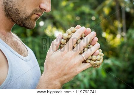 Young Man Holds A Rosary In His Hands And Pray