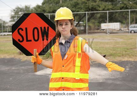 A female construction worker slowing traffic with a road sign and hand gesture.