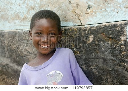 Smiling village girl by wooden boat