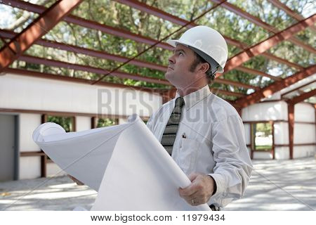 A construction inspector holding blueprints and looking at the roof beams of a steel building in progress.