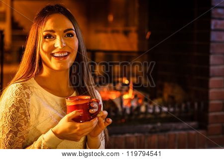 Happy Woman Drinking Coffee Relaxing At Fireplace.