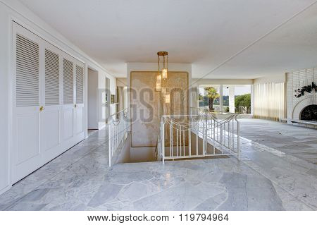 Unfurnished Hallway And Living Room With White Fenced Staircase, And Marble Floors.