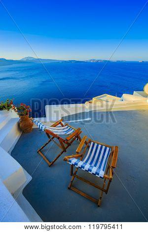 Beach chairs on the terrace at the beach, blue sky, sea and sun in Greece