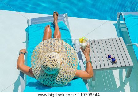 Pretty blond woman  enjoying a fresh cocktail in a swimming pool