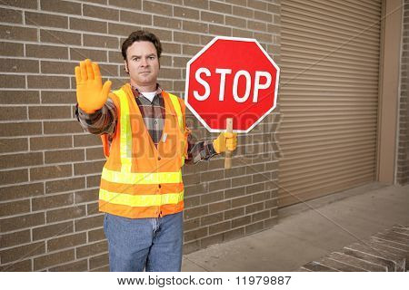 A school crossing guard holding a stop sign.  Room for text.