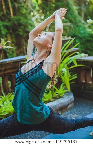 Young Woman Doing Yoga Outside In Natural Environment
