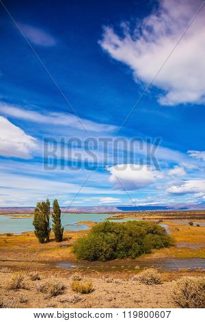 Yellow flat desert with shallow lakes. Argentine Patagonia on a windy day