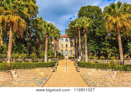 Catholic church dedicated to the Beatitudes. Stone path leading to the buildings of the monastery. Palm park gives light shade
