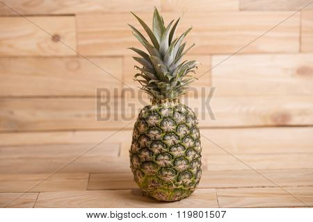 Pineapple on wooden table over a wooden background
