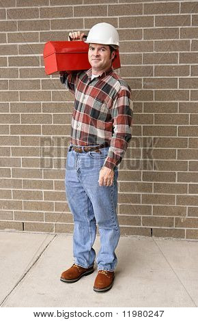 A full body view of a handsome blue collar worker with his toolbox and hardhat.
