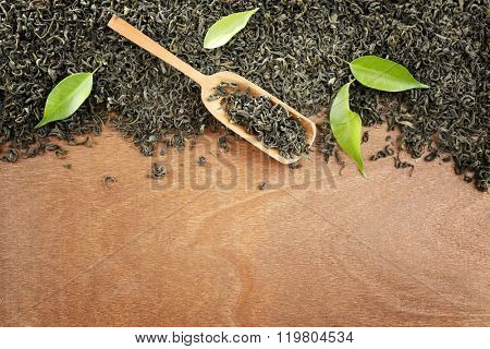 Scattered tea with green leaves on wooden table background, copy space