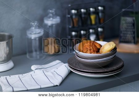 Utensils, towel and croissants on modern kitchen table, close up