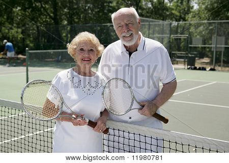 An attractive senior couple ready to play tennis.