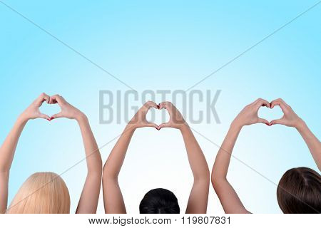 Young people makes hearts using fingers on blue background