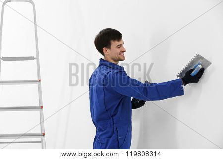 Worker renewing apartment on wall background