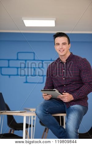 portrait of young business man in casual clothes sitting on table at  new startup office space