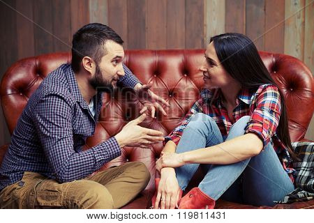 young couple sitting on sofa and have a interesting conversation