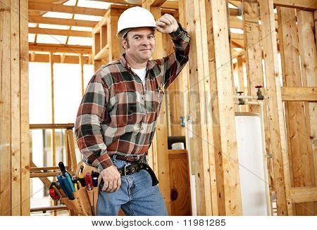 Ein Bauarbeiter mit seinen Werkzeugen auf der Baustelle.  Authentische Bauarbeiter auf tatsächliche const