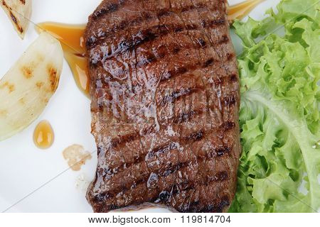 meat food : roast steak boneless with roast onion, served on green lettuce salad on dish isolated over white background