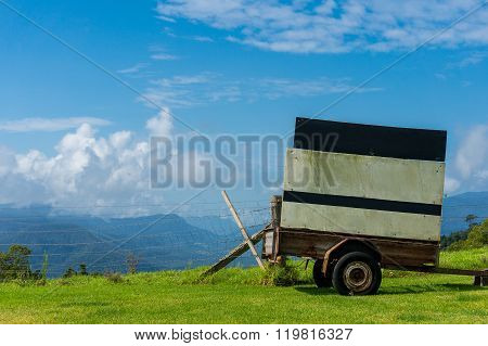 Cart with billboard against rural background