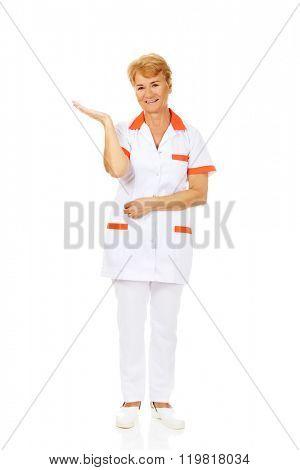 Smile elderly female doctor or nurse preseting something on open palm